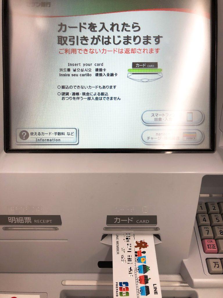 セブン銀行 ATM にカードを挿入する